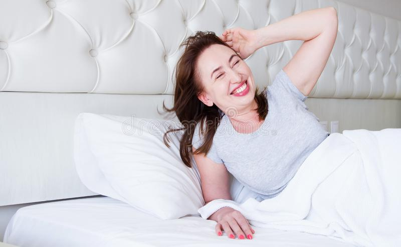 Happy middle aged woman lie in bed. Good morning and sleep concept. Menopause and healthy lifestyle. Selective focus. Banner.  stock photos