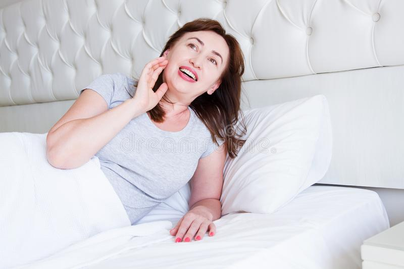 Happy middle aged woman lie in bed. Good morning and sleep concept. Menopause and healthy lifestyle. Selective focus.  stock photo