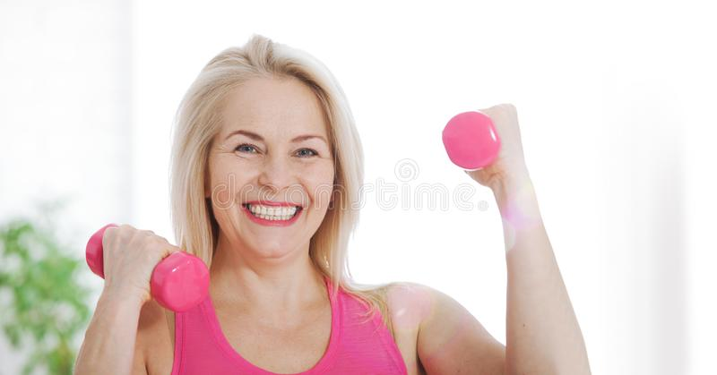 Happy middle aged woman lifting dumbbells at home in the living room stock photography
