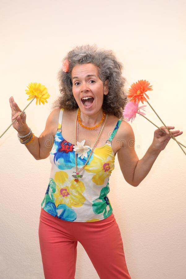 Open mouthed woman holding flowers Summer outfit. A happy middle-aged woman, open mouth, over fifty, with graying hair is holding textile flowers and is wearing stock images