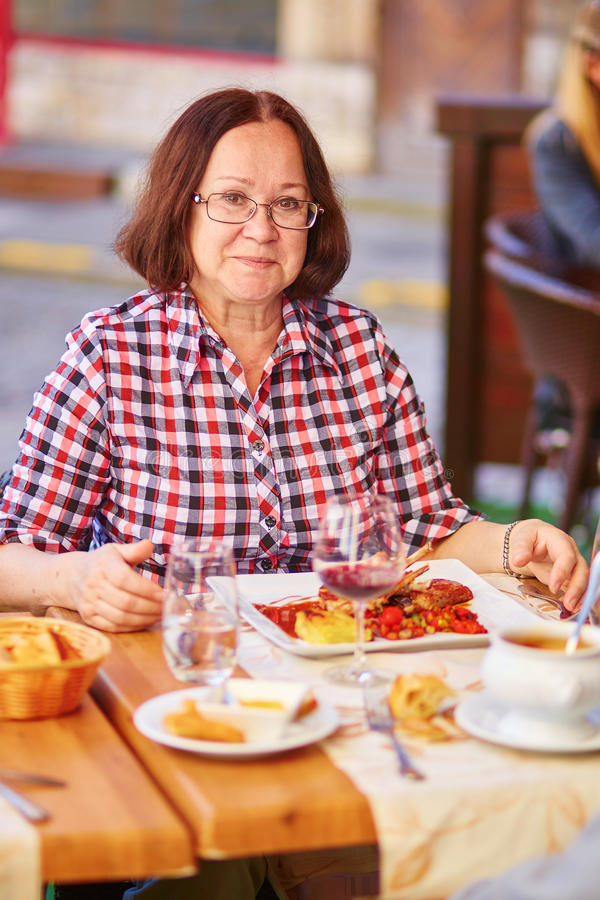 Happy middle aged woman in a restaurant. Happy middle aged woman in a French restaurant royalty free stock photography