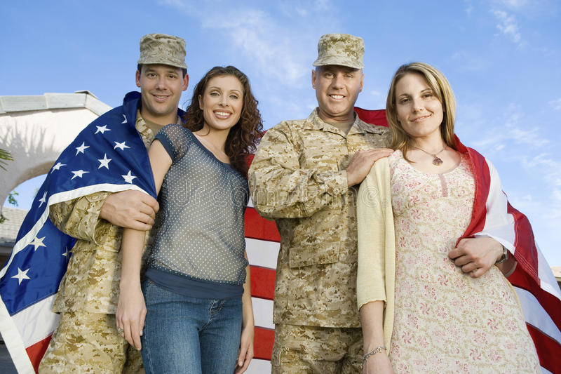 Happy Military Couples Wrapped In American Flag. Low angle portrait of happy military couples wrapped in American flag against sky stock photography