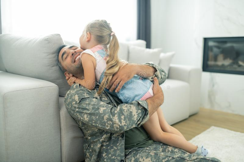 Happy military officer hugging his cute daughter tight royalty free stock photography