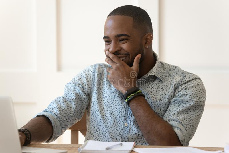 Happy millennial african american guy satisfied with online education result. stock image
