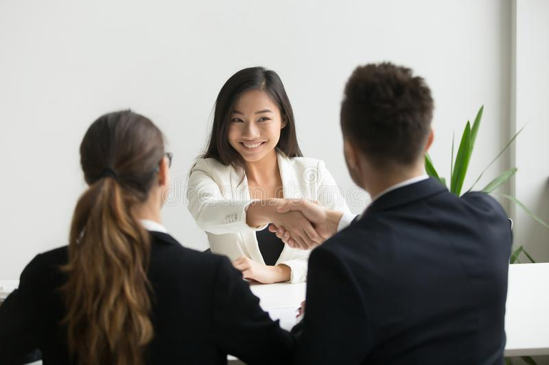 Happy millennial asian applicant getting hired shaking hand of h. R, employer handshaking successful smiling chinese candidate congratulating with job interview stock image