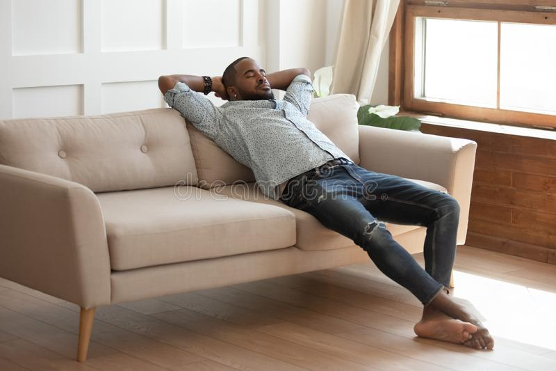 Happy millennial barefoot black guy daydreaming on sofa. stock photos