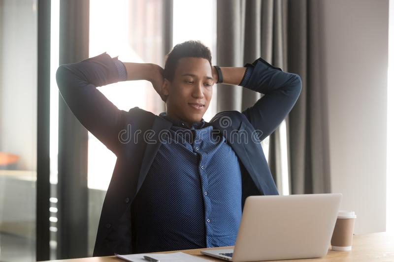 Happy millennial black businessman relaxing at office stock photography