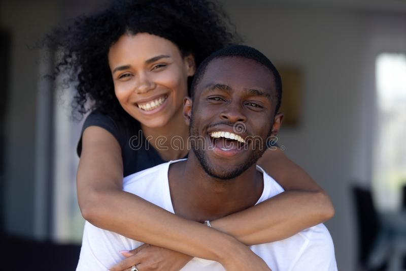 Happy millennial black couple laughing having fun outdoors, portrait royalty free stock photography