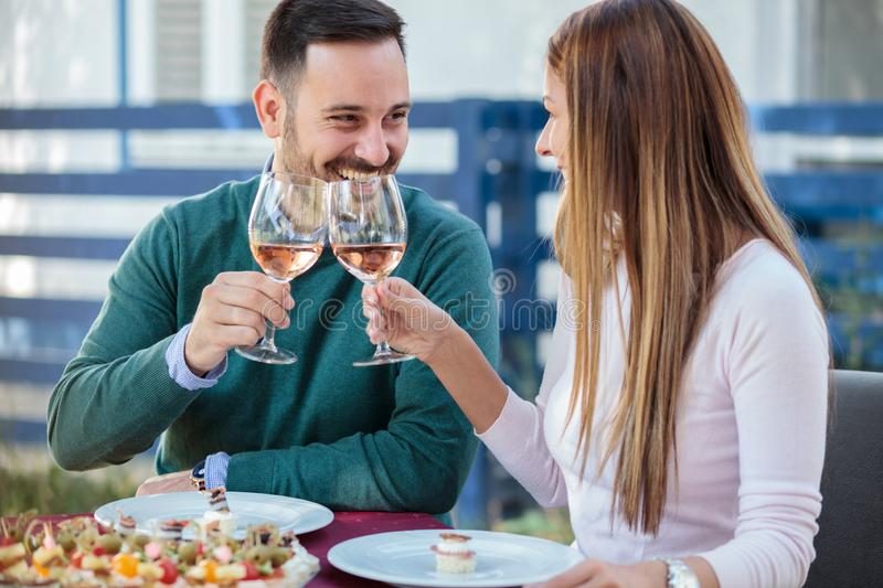 Happy millennial couple celebrating anniversary or birthday in a restaurant stock photo