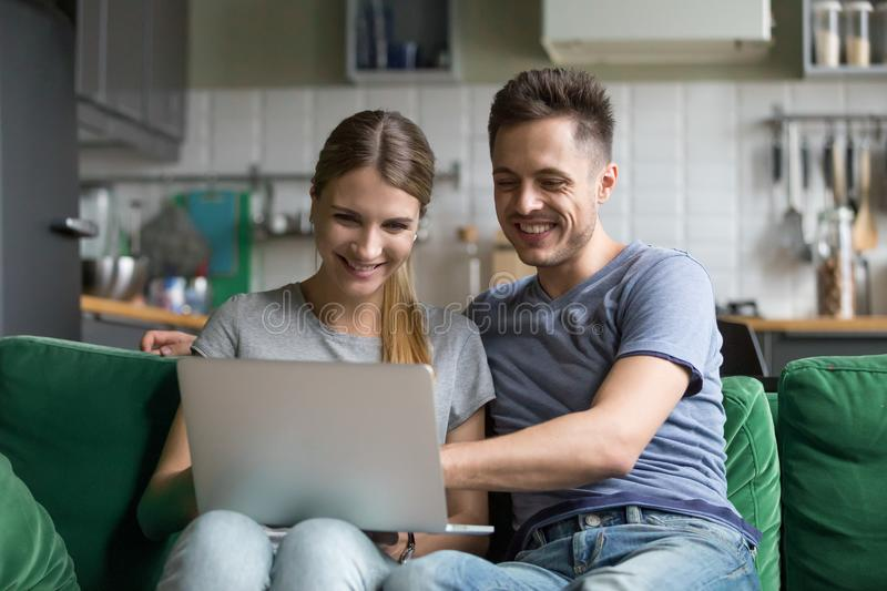 Happy couple laughing looking at laptop together watching funny stock images
