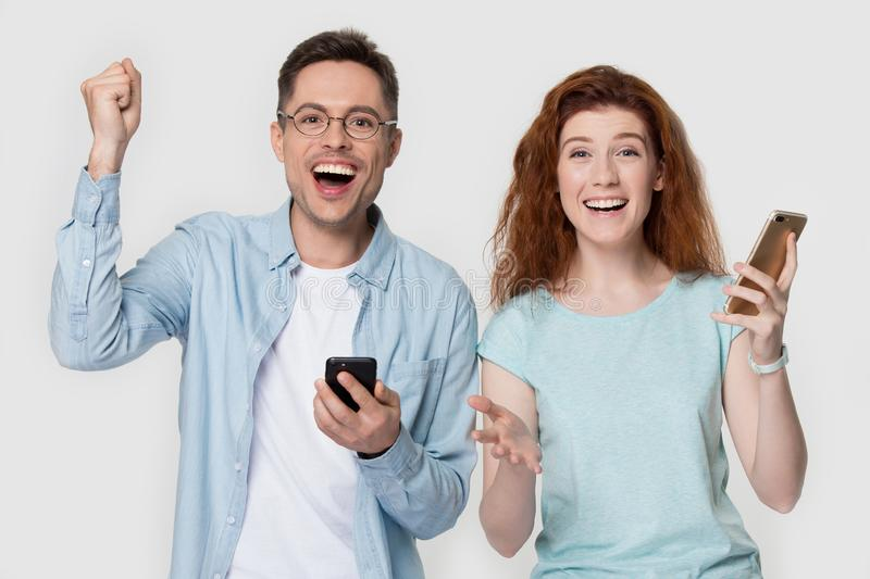 Happy millennial family couple received message with online lottery win. Overjoyed happy millennial family couple or friends holding smartphones, received stock images