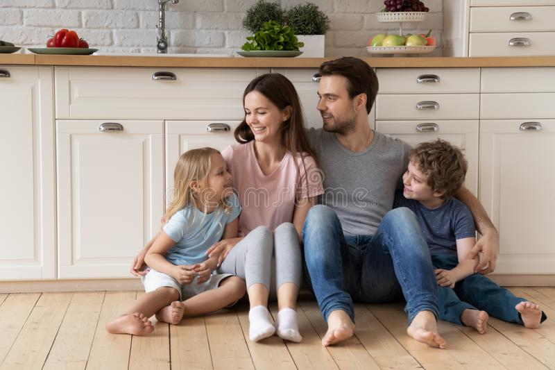 Happy millennial father mother and small kids sitting on floor. stock image