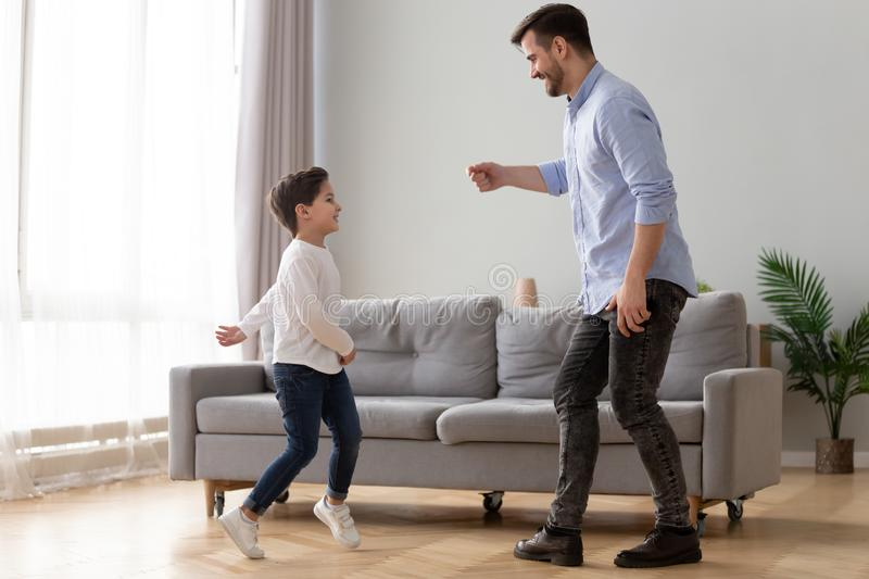 Happy young dad and preschooler son have fun at home stock photo