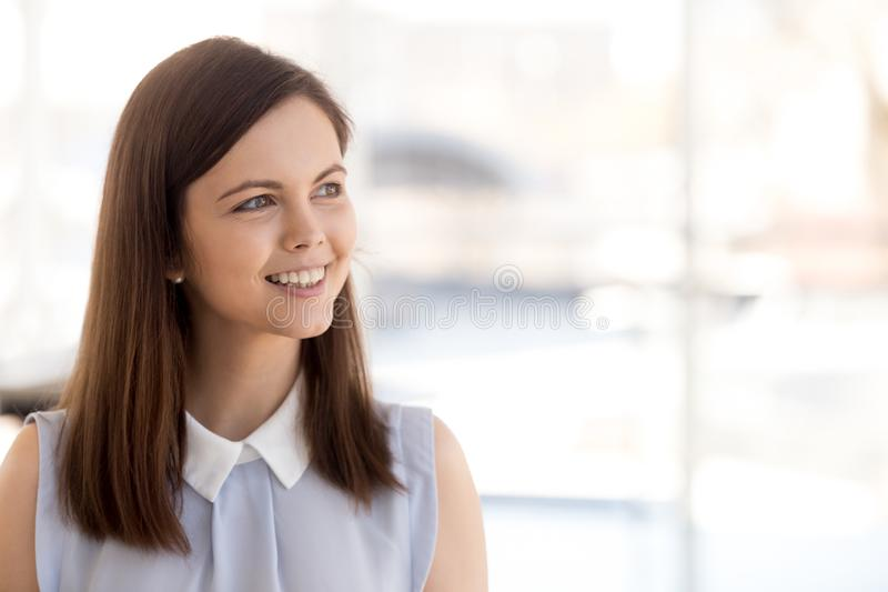Happy millennial female employee look in distance dreaming. Excited female employee look in distance dreaming about career success, dreamy millennial woman royalty free stock images