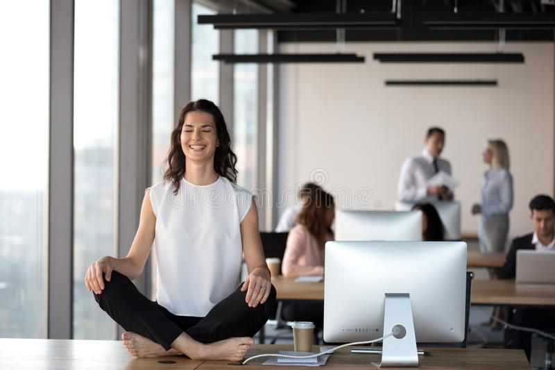 Happy female employee meditating at table in office stock image