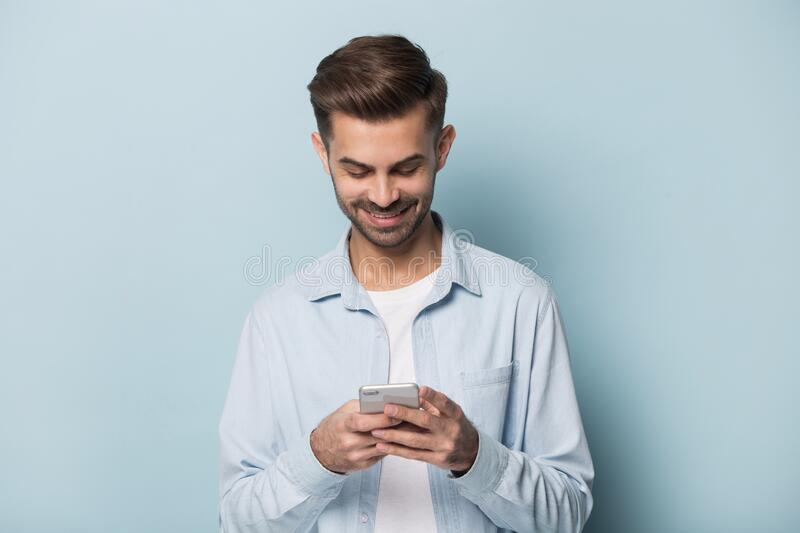Happy millennial guy holding smartphone in hands. stock image