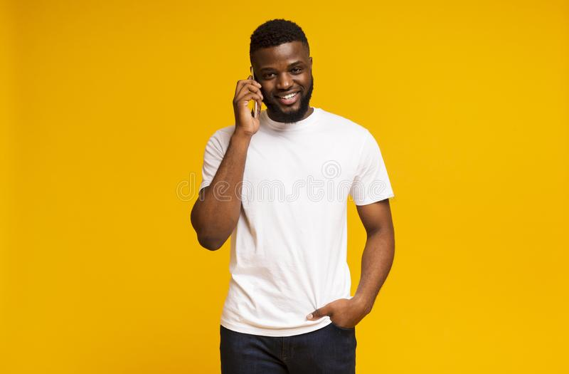 Happy Millennial Guy Talking On Mobile Phone And Smiling stock images