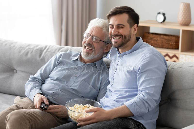 Happy millennial son and elderly dad have fun watching movie stock photos