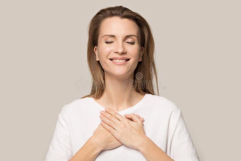 Happy millennial woman feel grateful showing love stock photo