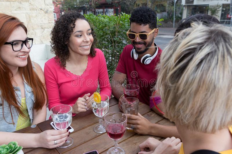 Mixed race group of friends having fun at restaurant outside. Sp stock image