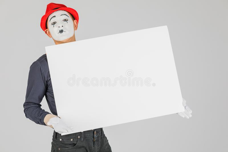 happy MIME artist holding a blank white Board, on a white background. stock images