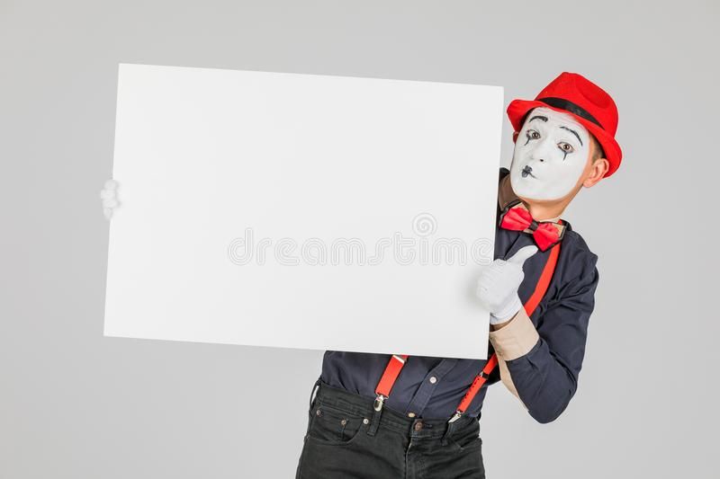 happy MIME artist holding a blank white Board, on a white background. stock photography