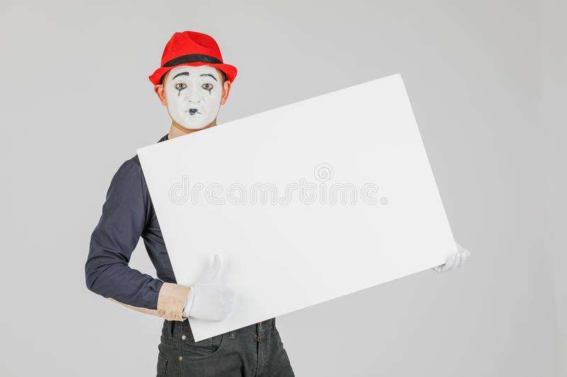 happy MIME artist holding a blank white Board, on a white background. royalty free stock images