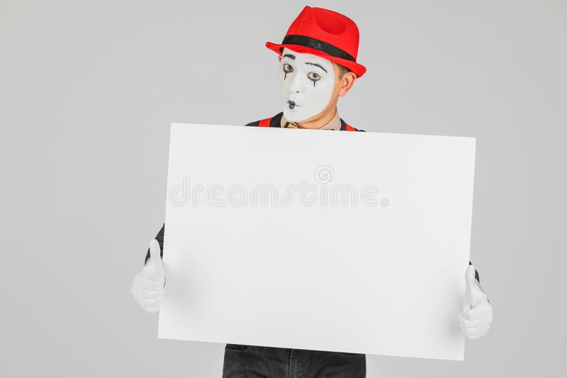 happy MIME artist holding a blank white Board, on a white background. stock photos