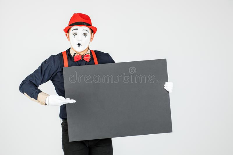 happy MIME artist holding a blank white Board, on a white background royalty free stock photos