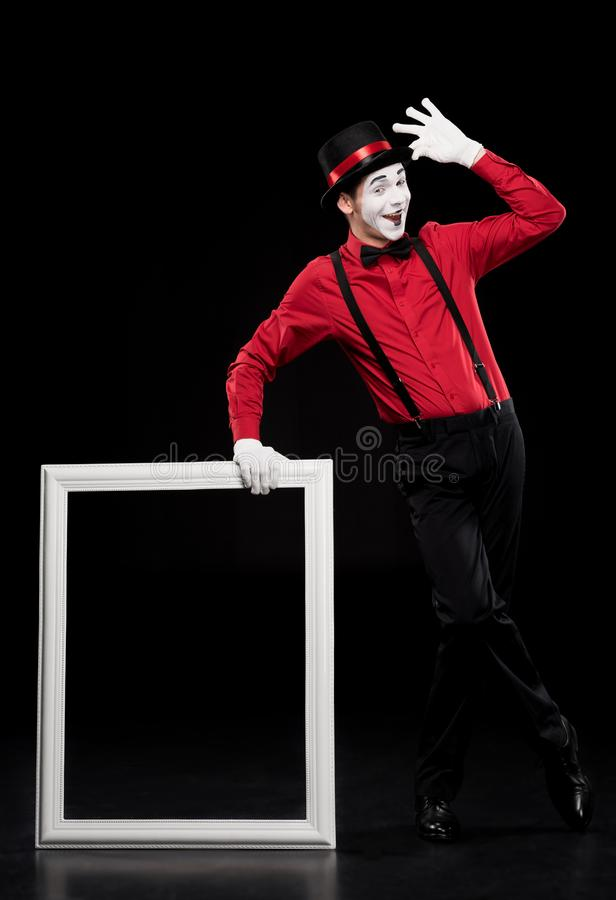 happy mime leaning on frame and waving hand royalty free stock photos