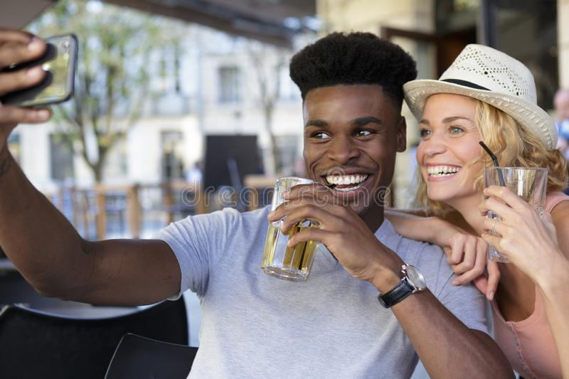 Happy mixed couple with drinks taking selfie royalty free stock photos
