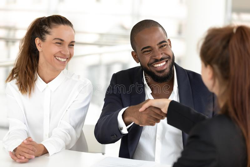 Happy mixed ethnicity couple clients handshake insurer realtor making deal. Happy mixed ethnicity couple clients handshake insurer realtor broker make agreement royalty free stock photography