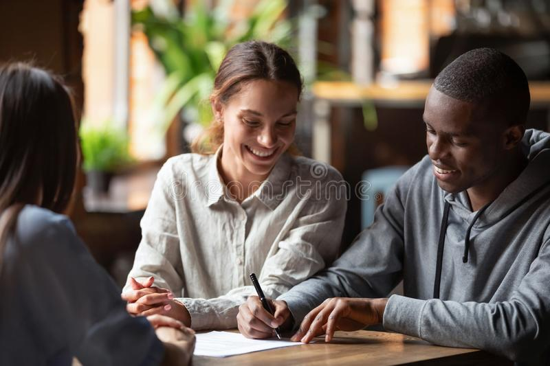 Happy mixed ethnicity couple customers sign mortgage loan contract. Smiling interracial husband and wife make insurance investment deal put signature on paper royalty free stock photography