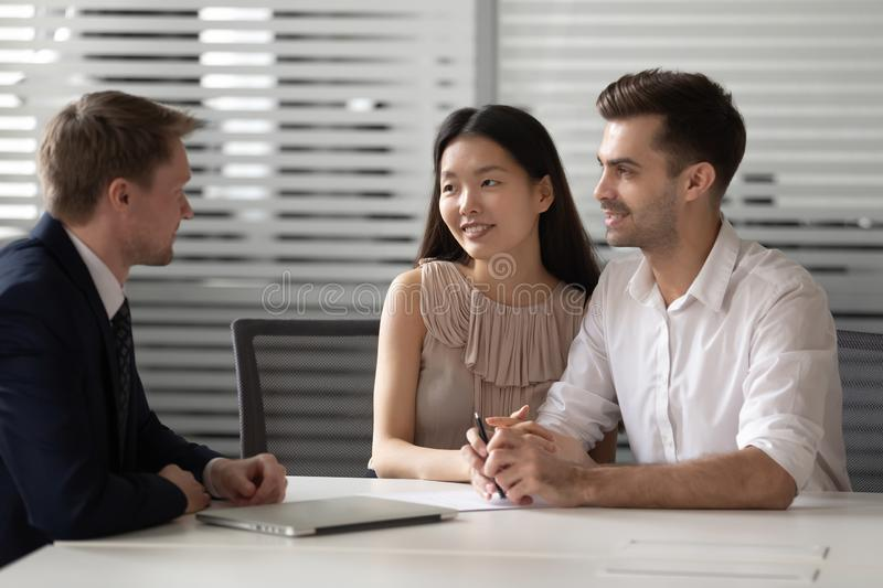 Happy mixed ethnicity couple customers talk to lawyer bank manager. At meeting consulting about investment insurance real estate deal, young family clients royalty free stock photo