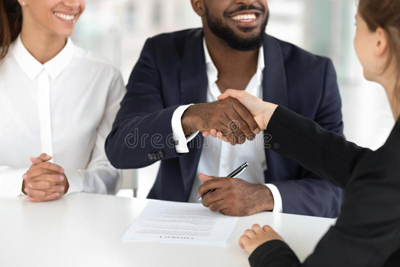 Happy mixed ethnicity couple handshaking broker sign mortgage contract. Happy mixed ethnicity couple make real estate insurance deal sign mortgage bank loan royalty free stock image