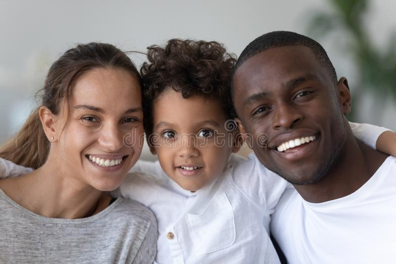 Happy mixed ethnicity family with cute kid son bonding, portrait royalty free stock images