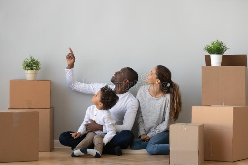 Happy mixed ethnicity family discuss new home sit with boxes stock photos