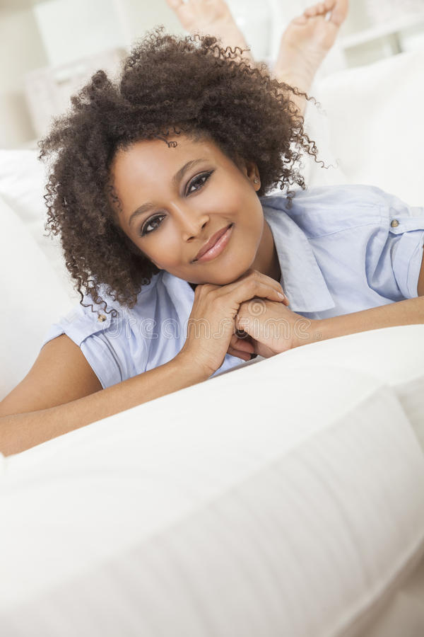 Happy Mixed Race African American Girl Young Woman. A beautiful mixed race African American girl or young woman laying down on sofa at home looking happy and royalty free stock image