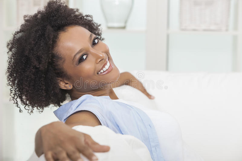 Happy Mixed Race African American Girl Young Woman. A beautiful mixed race African American girl or young woman sitting on sofa at home looking happy and relaxed royalty free stock photos