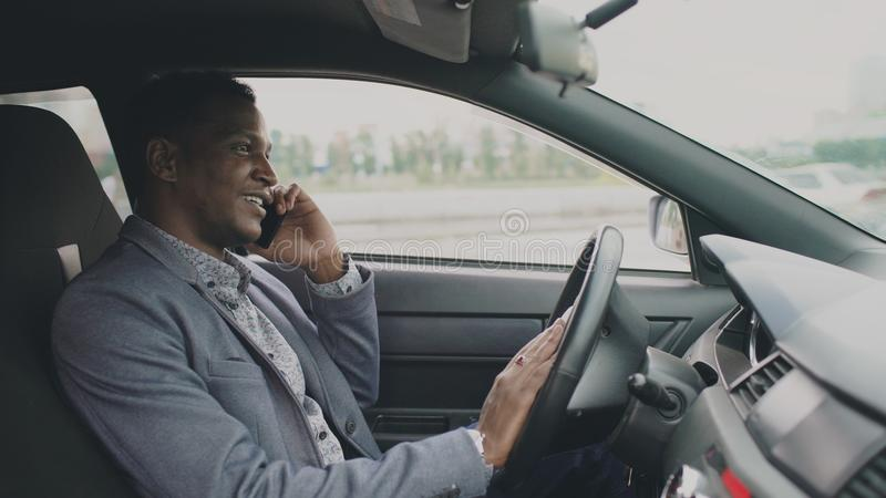 Happy mixed race businessman talking phone while sitting inside his car outdoors stock photos
