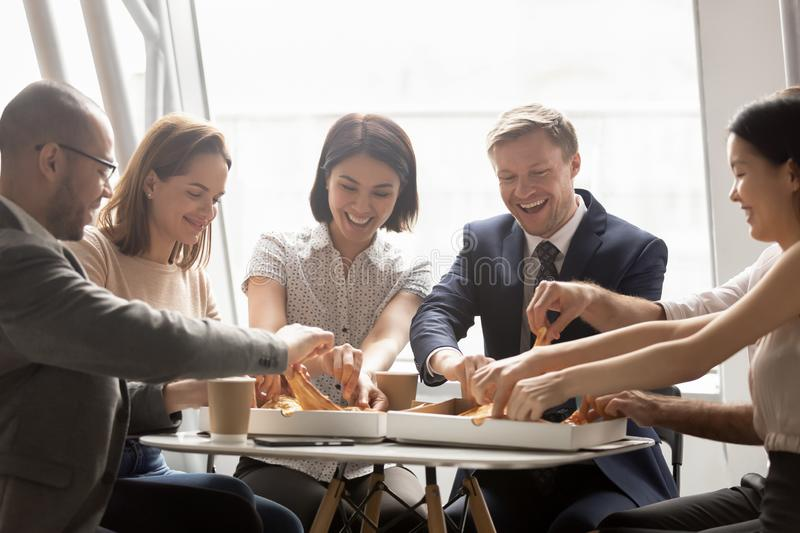 Happy mixed race company workers sharing lunch, eating pizza. stock photos