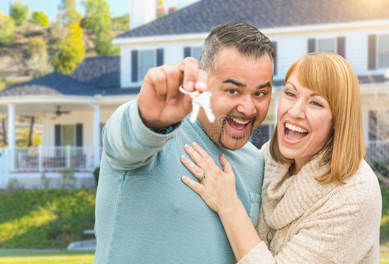 Happy Mixed Race Couple in Front of House with New Keys. Happy Mixed Race Couple in Front of New Home with House Keys stock photos