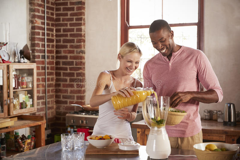Happy mixed race couple making smoothies, pouring juice royalty free stock photo