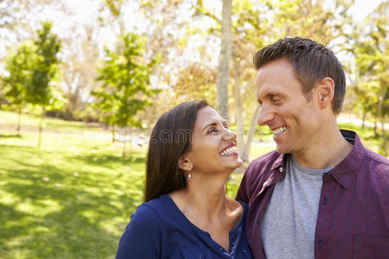 Happy mixed race couple in park looking at each other royalty free stock image
