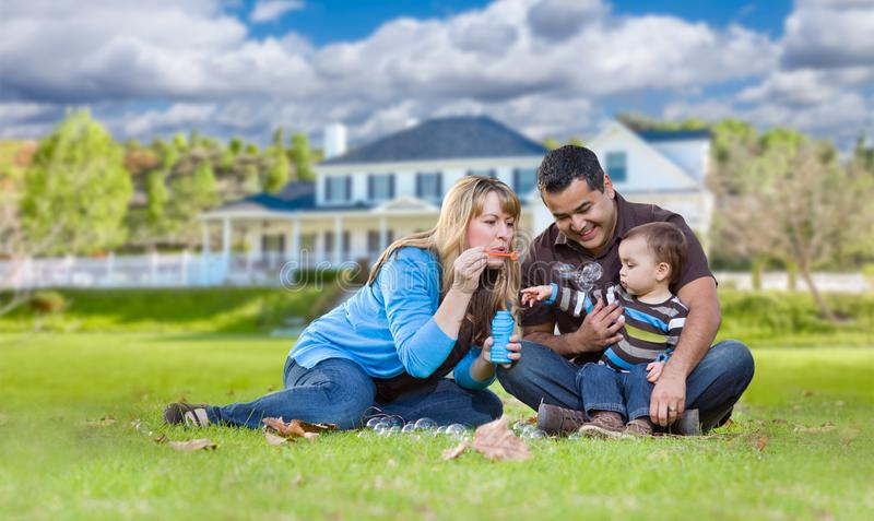 Happy Mixed Race Ethnic Family Playing with Bubbles In Front Yard. Happy Mixed Race Ethnic Family Playing with Bubbles In Their Front Yard stock images