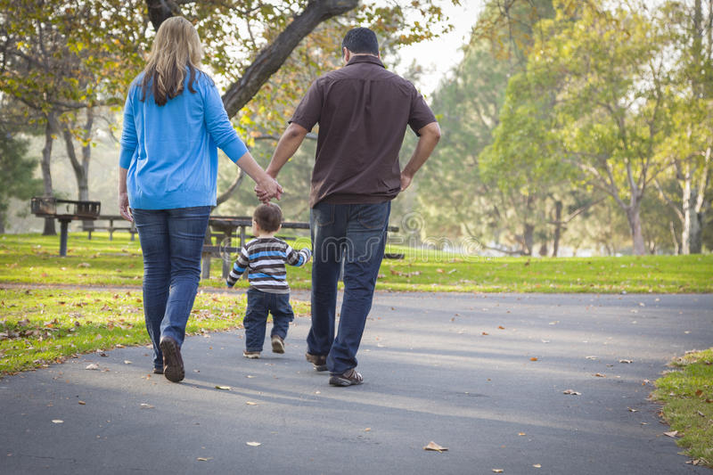 Happy Mixed Race Ethnic Family Walking In The Park. Happy Young Mixed Race Ethnic Family Walking In The Park royalty free stock photos