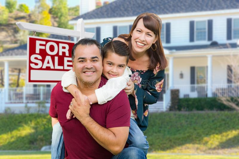 Happy Mixed Race Family In Front of House and For Sale Real Estate Sign stock photos
