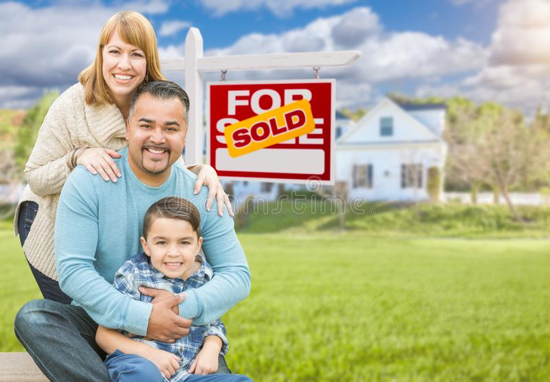Mixed Race Family In Front of House and Sold For Sale Real Estate Sign. Happy Mixed Race Hispanic and Caucasian Family Portrait In Front of House and Sold For stock photography