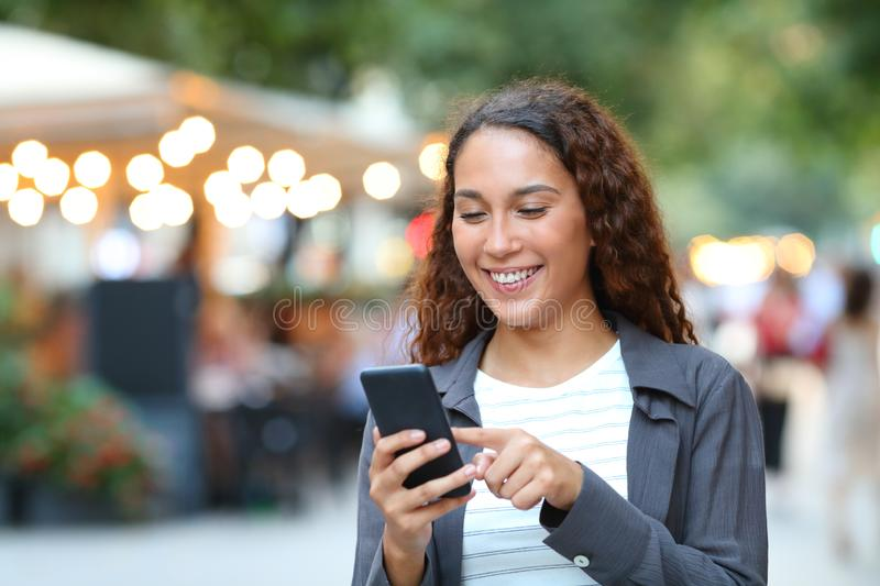 Happy mixed race woman using smart phone royalty free stock image