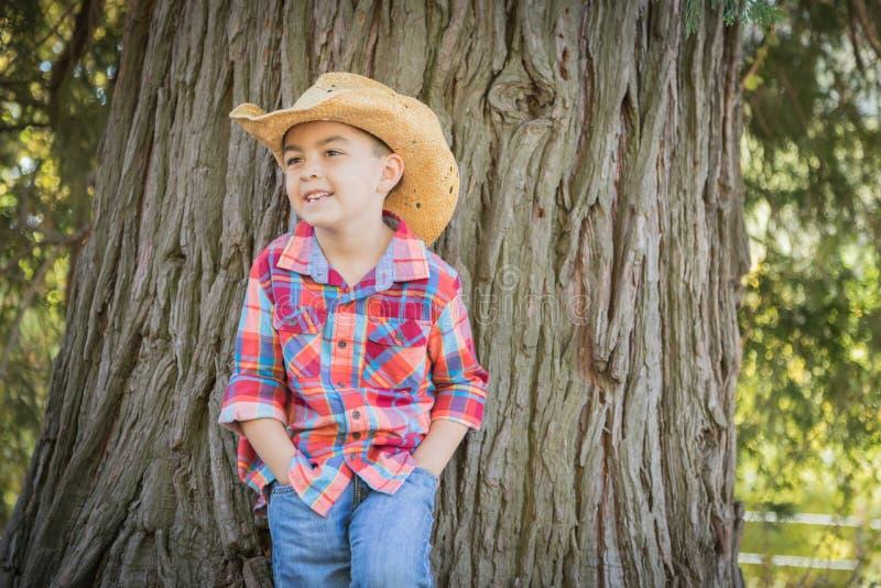 Happy Mixed Race Young Boy Wearing Cowboy Hat Standing Outdoors. Mixed Race Young Boy Wearing Cowboy Hat Standing Outdoors stock images